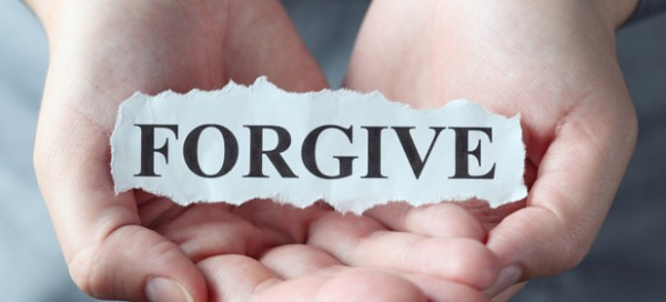 """Torn piece of paper with the word """"Forgive"""" in the woman's palms."""